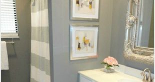 Painting the bathroom cabinets and adding a soft color to the wall .